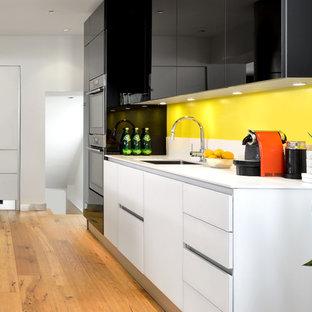 Idee per una cucina minimalista con lavello sottopiano, ante lisce, ante nere, top in quarzite, paraspruzzi giallo, elettrodomestici in acciaio inossidabile, parquet chiaro e un'isola