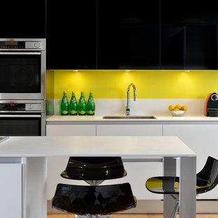 Offene, Zweizeilige Moderne Küche mit Unterbauwaschbecken, flächenbündigen Schrankfronten, schwarzen Schränken, Quarzit-Arbeitsplatte, Küchenrückwand in Gelb, Küchengeräten aus Edelstahl, hellem Holzboden und Kücheninsel in Toronto