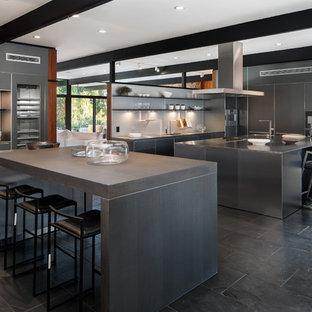 Huge contemporary kitchen ideas - Example of a huge trendy galley black floor kitchen design in Los Angeles with flat-panel cabinets, gray cabinets, stainless steel countertops, white backsplash, stainless steel appliances and two islands