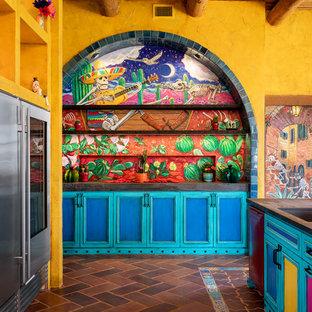 サンディエゴの広いサンタフェスタイルのおしゃれなキッチン (アンダーカウンターシンク、シェーカースタイル扉のキャビネット、マルチカラーのキッチンパネル、テラコッタタイルの床、黒いキッチンカウンター、赤いキャビネット、木材カウンター、セメントタイルのキッチンパネル、カラー調理設備、茶色い床) の写真