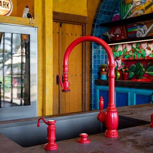 サンディエゴの広いサンタフェスタイルのおしゃれなキッチン (アンダーカウンターシンク、シェーカースタイル扉のキャビネット、赤いキャビネット、木材カウンター、マルチカラーのキッチンパネル、セメントタイルのキッチンパネル、カラー調理設備、テラコッタタイルの床、茶色い床、黒いキッチンカウンター) の写真