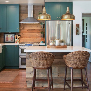 Coastal kitchen remodeling - Example of a beach style l-shaped medium tone wood floor and brown floor kitchen design in San Diego with a farmhouse sink, shaker cabinets, turquoise cabinets, brown backsplash, wood backsplash, stainless steel appliances, an island and white countertops