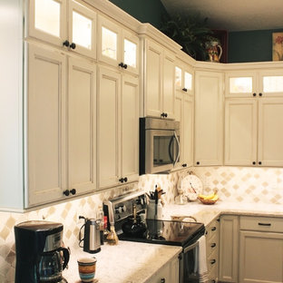 Inspiration for a mid-sized country l-shaped eat-in kitchen in Boise with a farmhouse sink, recessed-panel cabinets, beige cabinets, quartz benchtops, beige splashback, mosaic tile splashback, stainless steel appliances, vinyl floors, with island and brown floor.