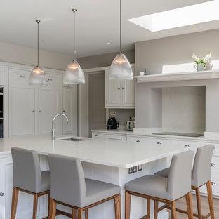 Bild på ett stort vintage vit vitt kök, med vita skåp, bänkskiva i kvartsit, grått stänkskydd, laminatgolv, en köksö, stänkskydd i marmor, en undermonterad diskho, luckor med infälld panel, integrerade vitvaror och beiget golv