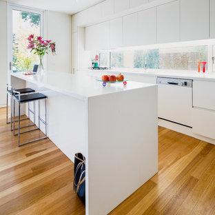 キャンベラの中くらいのコンテンポラリースタイルのおしゃれなキッチン (白いキャビネット、クオーツストーンカウンター、ガラスまたは窓のキッチンパネル、白い調理設備、無垢フローリング、茶色い床、白いキッチンカウンター、フラットパネル扉のキャビネット) の写真
