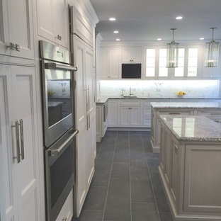 Design ideas for a transitional l-shaped kitchen in Orange County with recessed-panel cabinets, white cabinets, granite benchtops, stone slab splashback, stainless steel appliances, porcelain floors, multiple islands and grey floor.