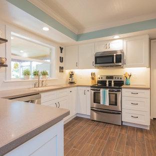 他の地域の小さいカントリー風おしゃれなキッチン (アンダーカウンターシンク、シェーカースタイル扉のキャビネット、白いキャビネット、人工大理石カウンター、白いキッチンパネル、セラミックタイルのキッチンパネル、シルバーの調理設備の、セラミックタイルの床、茶色い床) の写真