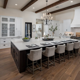 Southwestern kitchen appliance - Kitchen - southwestern medium tone wood floor and brown floor kitchen idea in Phoenix with shaker cabinets, white cabinets, gray backsplash, stainless steel appliances, an island and white countertops