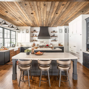 Cottage u-shaped dark wood floor and brown floor kitchen photo in Salt Lake City with a farmhouse sink, shaker cabinets, gray cabinets, stainless steel appliances, two islands and white countertops