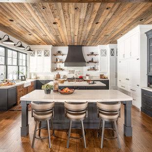 Réalisation d'une cuisine champêtre en U avec un évier de ferme, un placard à porte shaker, des portes de placard grises, un électroménager en acier inoxydable, un sol en bois foncé, 2 îlots, un sol marron et un plan de travail blanc.