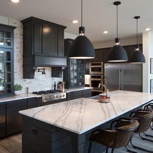 Klassische Küche in L-Form mit Landhausspüle, Schrankfronten mit vertiefter Füllung, schwarzen Schränken, Küchenrückwand in Weiß, Rückwand aus Mosaikfliesen, Küchengeräten aus Edelstahl, braunem Holzboden, Kücheninsel, braunem Boden und weißer Arbeitsplatte in Dallas