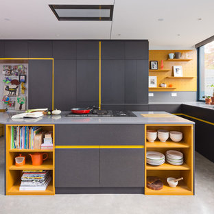This is an example of a contemporary l-shaped kitchen in London with an undermount sink, flat-panel cabinets, yellow cabinets, with island and grey floor.