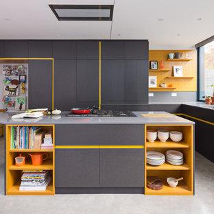 Moderne Küche in L-Form mit Unterbauwaschbecken, flächenbündigen Schrankfronten, gelben Schränken, Kücheninsel und grauem Boden in London