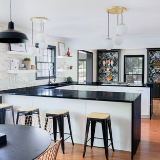 Photo of a transitional u-shaped eat-in kitchen in Other with a single-bowl sink, shaker cabinets, white cabinets, multi-coloured splashback, medium hardwood floors, a peninsula and black benchtop.