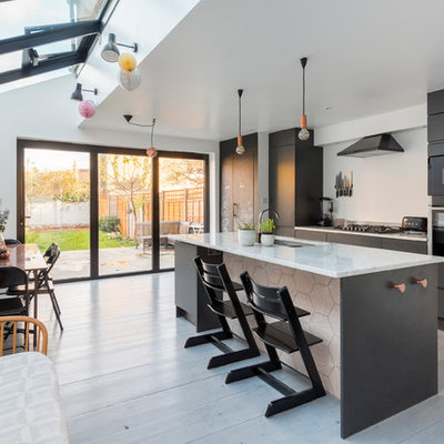 Eat-in kitchen - mid-sized contemporary single-wall light wood floor and white floor eat-in kitchen idea in London with flat-panel cabinets, black cabinets, marble countertops and an island