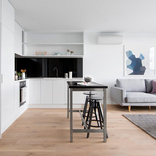 Design ideas for a contemporary l-shaped open plan kitchen in Melbourne with open cabinets, white cabinets, black splashback, light hardwood floors and with island.