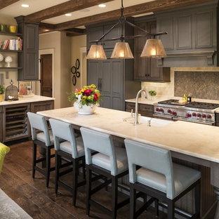 Mittelgroße Klassische Wohnküche in L-Form mit Landhausspüle, Schrankfronten mit vertiefter Füllung, dunklen Holzschränken, Kalkstein-Arbeitsplatte, Küchengeräten aus Edelstahl, dunklem Holzboden, Kücheninsel, Küchenrückwand in Beige, braunem Boden und Kalk-Rückwand in Minneapolis