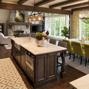 Inspiration for a mid-sized traditional single-wall eat-in kitchen in Minneapolis with a farmhouse sink, flat-panel cabinets, medium wood cabinets, limestone benchtops, stainless steel appliances, medium hardwood floors, with island, beige splashback and mosaic tile splashback.