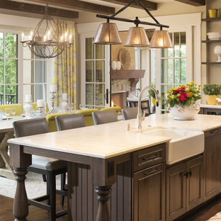 Design ideas for a mid-sized traditional single-wall eat-in kitchen in Minneapolis with a farmhouse sink, flat-panel cabinets, medium wood cabinets, limestone benchtops, stainless steel appliances, medium hardwood floors and with island.