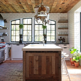 Contemporary kitchen photos - Inspiration for a contemporary l-shaped brick floor kitchen remodel in Chicago with flat-panel cabinets, white cabinets, white backsplash, subway tile backsplash and stainless steel appliances