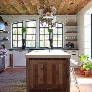 Cette photo montre une cuisine tendance en L avec un placard à porte plane, des portes de placard blanches, une crédence blanche, une crédence en carrelage métro, un électroménager en acier inoxydable et un sol en brique.