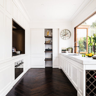 Inspiration for a large traditional u-shaped separate kitchen in Melbourne with white cabinets, marble benchtops, dark hardwood floors, brown floor, an undermount sink, black appliances, raised-panel cabinets, white splashback, marble splashback and no island.