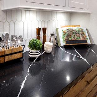 オクラホマシティの大きいカントリー風おしゃれなキッチン (アンダーカウンターシンク、白いキャビネット、クオーツストーンカウンター、白いキッチンパネル、磁器タイルのキッチンパネル、パネルと同色の調理設備、大理石の床、黒いキッチンカウンター) の写真