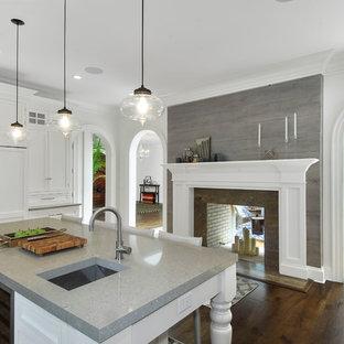 ニューヨークの大きい地中海スタイルのおしゃれなキッチン (アンダーカウンターシンク、シェーカースタイル扉のキャビネット、白いキャビネット、クオーツストーンカウンター、パネルと同色の調理設備、無垢フローリング) の写真