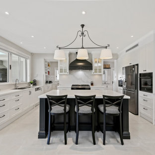 Inspiration for a large transitional u-shaped eat-in kitchen in Sydney with a double-bowl sink, beaded inset cabinets, white cabinets, quartz benchtops, white splashback, subway tile splashback, stainless steel appliances, ceramic floors, with island, white floor and white benchtop.