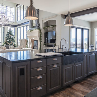Photo of an expansive industrial open plan kitchen in Denver with a farmhouse sink, raised-panel cabinets, white cabinets, soapstone benchtops, white splashback, ceramic splashback, stainless steel appliances and medium hardwood floors.