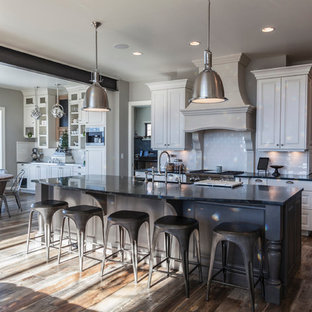 Huge industrial open concept kitchen pictures - Inspiration for a huge industrial medium tone wood floor open concept kitchen remodel in Denver with a farmhouse sink, raised-panel cabinets, white cabinets, soapstone countertops, white backsplash, ceramic backsplash and stainless steel appliances