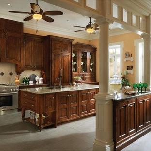 ヒューストンの巨大なヴィクトリアン調のおしゃれなキッチン (ガラス扉のキャビネット、中間色木目調キャビネット、人工大理石カウンター、シルバーの調理設備の、セラミックタイルの床、ドロップインシンク、ベージュキッチンパネル、セラミックタイルのキッチンパネル) の写真