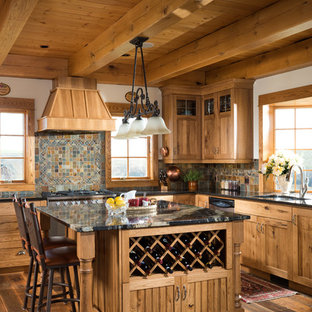 This is an example of a traditional l-shaped eat-in kitchen in Calgary with medium wood cabinets, stainless steel appliances, with island, an undermount sink, recessed-panel cabinets, multi-coloured splashback, medium hardwood floors and slate splashback.
