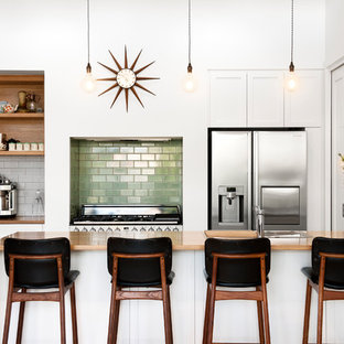 Photo of a contemporary galley kitchen in Adelaide with a drop-in sink, flat-panel cabinets, white cabinets, wood benchtops, green splashback, subway tile splashback, stainless steel appliances, a peninsula, beige floor and brown benchtop.