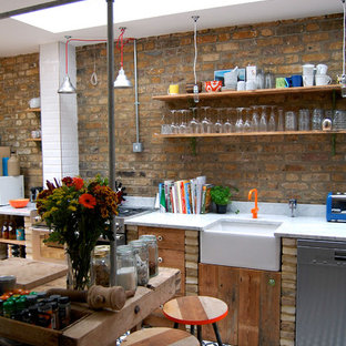 ロンドンのエクレクティックスタイルのおしゃれなアイランドキッチン (エプロンフロントシンク、ヴィンテージ仕上げキャビネット、サブウェイタイルのキッチンパネル、シルバーの調理設備の) の写真