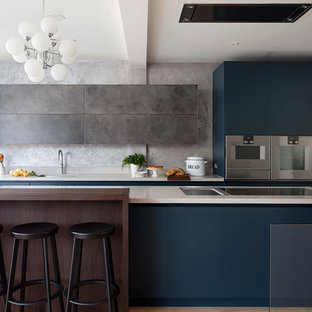 Design ideas for a large contemporary galley kitchen in London with a submerged sink, engineered stone countertops, grey splashback, light hardwood flooring, an island, beige floors, white worktops, flat-panel cabinets, blue cabinets and stainless steel appliances.