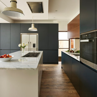Inspiration for a large contemporary l-shaped eat-in kitchen in London with an integrated sink, blue cabinets, marble benchtops, metallic splashback, mirror splashback, light hardwood floors, with island, brown floor and white benchtop.