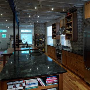 シカゴの大きいインダストリアルスタイルのおしゃれなキッチン (アンダーカウンターシンク、シェーカースタイル扉のキャビネット、中間色木目調キャビネット、御影石カウンター、白いキッチンパネル、石タイルのキッチンパネル、シルバーの調理設備の、無垢フローリング) の写真