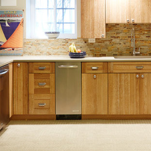Design ideas for a large traditional l-shaped eat-in kitchen in Chicago with an undermount sink, flat-panel cabinets, white cabinets, solid surface benchtops, grey splashback, stone tile splashback, stainless steel appliances and carpet.