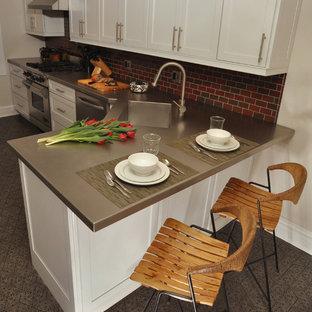 Zweizeilige, Mittelgroße Moderne Wohnküche mit Küchengeräten aus Edelstahl, Edelstahl-Arbeitsplatte, integriertem Waschbecken, Schrankfronten im Shaker-Stil, weißen Schränken, Küchenrückwand in Rot, Rückwand aus Metrofliesen, Betonboden und Halbinsel in Chicago