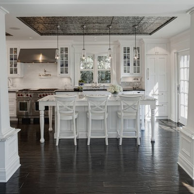 Elegant kitchen photo in Chicago with stainless steel appliances, glass-front cabinets, white cabinets, white backsplash and subway tile backsplash