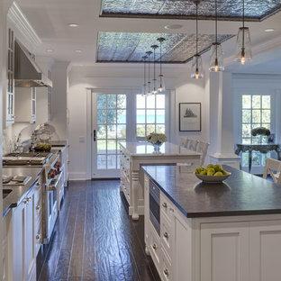 Ejemplo de cocina clásica con armarios con paneles empotrados, puertas de armario blancas, dos o más islas y encimeras negras