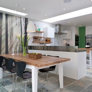 Новые идеи обустройства дома: кухня среднего размера в современном стиле с обеденным столом, монолитной раковиной, плоскими фасадами, белыми фасадами, столешницей из дерева, белым фартуком, техникой из нержавеющей стали, островом и фартуком из плитки кабанчик