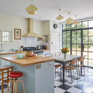 Offene Stilmix Küche mit Schrankfronten im Shaker-Stil, blauen Schränken, Arbeitsplatte aus Holz, Kücheninsel, Doppelwaschbecken, Küchenrückwand in Weiß, Rückwand aus Metrofliesen und buntem Boden in Oxfordshire