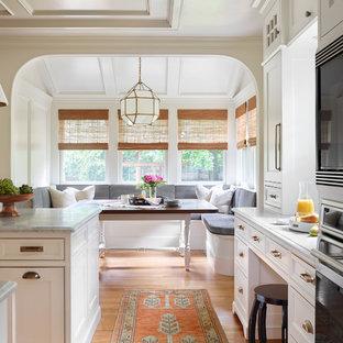 Klassisk inredning av ett stort grå grått kök och matrum, med en undermonterad diskho, luckor med profilerade fronter, vita skåp, marmorbänkskiva, vitt stänkskydd, stänkskydd i marmor, integrerade vitvaror, mellanmörkt trägolv, en köksö och brunt golv