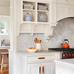 Foto di una grande cucina chic con lavello sottopiano, ante a filo, ante bianche, top in marmo, paraspruzzi bianco, paraspruzzi in lastra di pietra, elettrodomestici da incasso, pavimento in legno massello medio, isola, pavimento marrone e top grigio