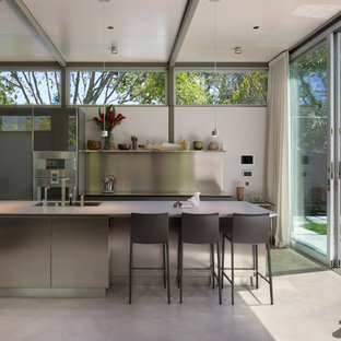 Inspiration for a mid-sized modern single-wall open plan kitchen in San Francisco with a double-bowl sink, flat-panel cabinets, stainless steel cabinets, concrete benchtops, white splashback, stainless steel appliances, concrete floors and with island.