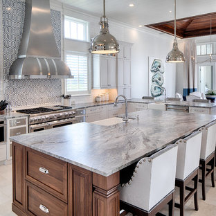 Beach style eat-in kitchen remodeling - Example of a coastal beige floor eat-in kitchen design in Atlanta with a farmhouse sink, recessed-panel cabinets, white cabinets, multicolored backsplash, stainless steel appliances, an island and gray countertops