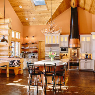 Photo of an expansive country u-shaped eat-in kitchen in Denver with an undermount sink, raised-panel cabinets, beige cabinets, quartz benchtops, multi-coloured splashback, stone tile splashback, stainless steel appliances, slate floors and with island.