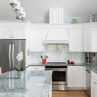 Photo of a large traditional l-shaped open plan kitchen in Portland Maine with a drop-in sink, shaker cabinets, white cabinets, granite benchtops, white splashback, subway tile splashback, stainless steel appliances, vinyl floors, with island and brown floor.